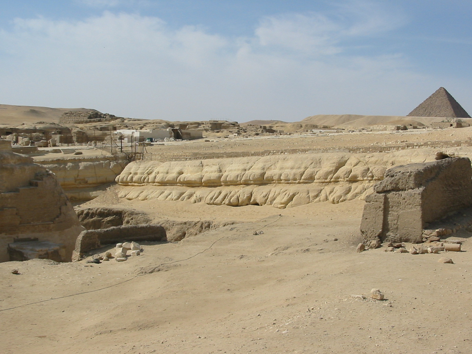 the western wall of the sphinx enclosure, showing erosion consistently along its length